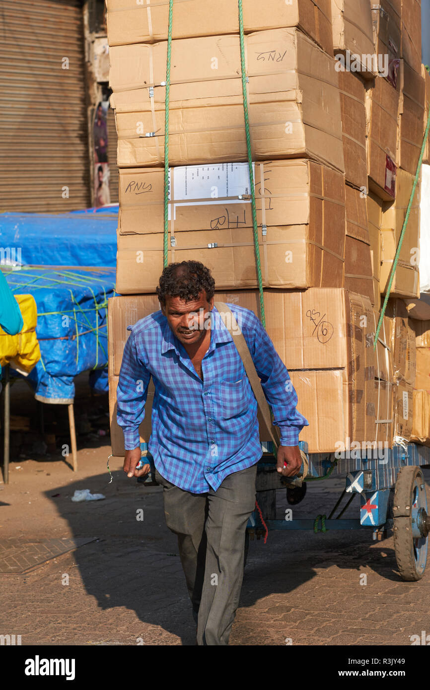 A handcart puller in Mumbai, India, pulls a cart with a load multiple his own weight; some pullers pull up to a ton - Stock Image