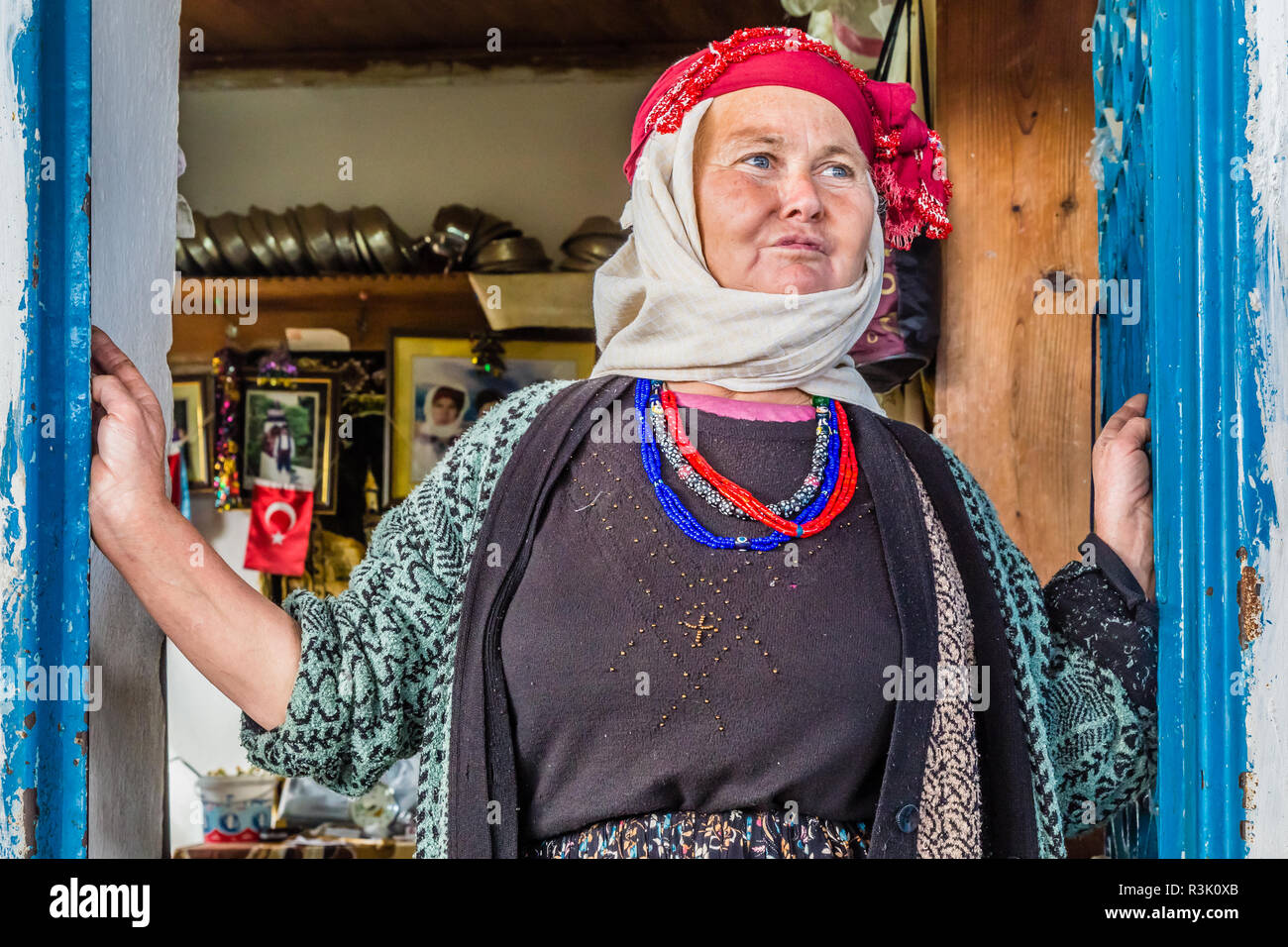 Comakdag Kizilagac, Western Anatolia, Turkey, February 23, 2013:  Village woman looking out of the door to her house. - Stock Image