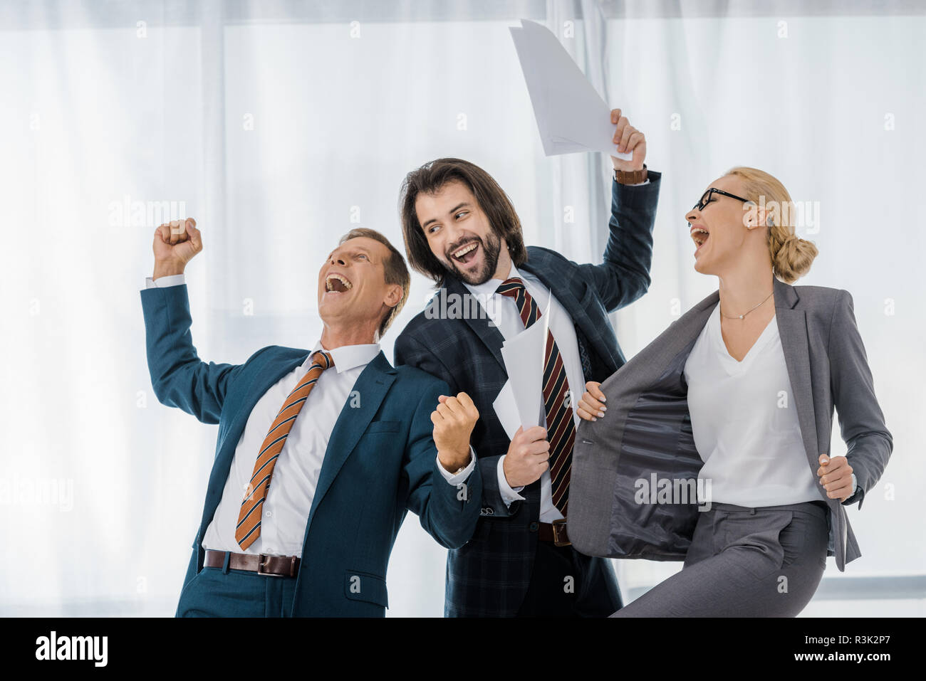 happy office workers rejoicing great deal in office - Stock Image