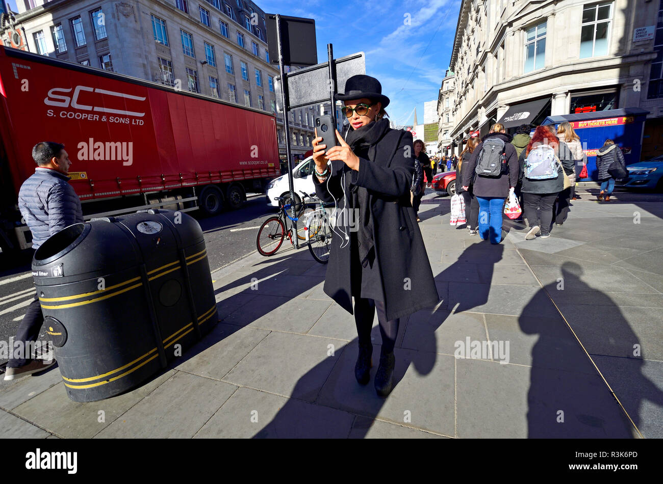 London, England, UK. Woman wearing a hat, filming on her mobile phone while walking - Stock Image