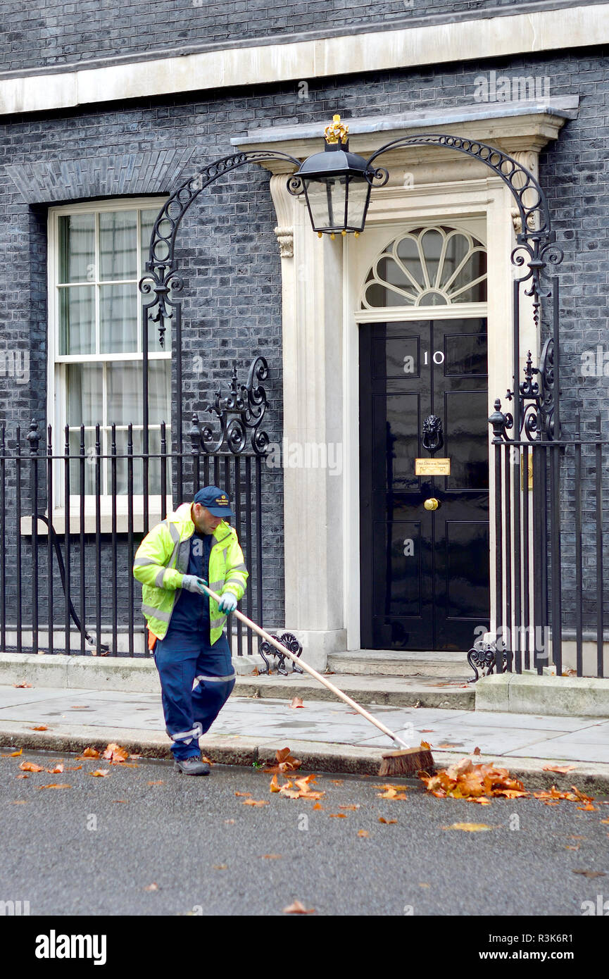 Cleaner sweeping up fallen autumn leaves outside No 10 Downing Street, London, England, UK. - Stock Image