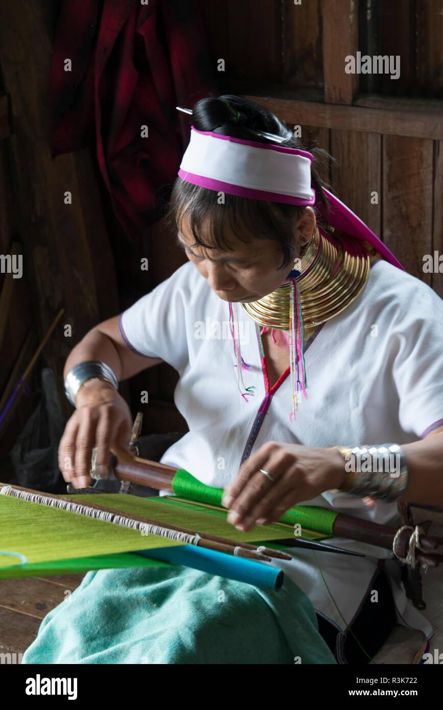 Padaung (Kayan Lahwi) woman wearing brass neck coils weaving, Inle Lake, Shan State, Myanmar Stock Photo