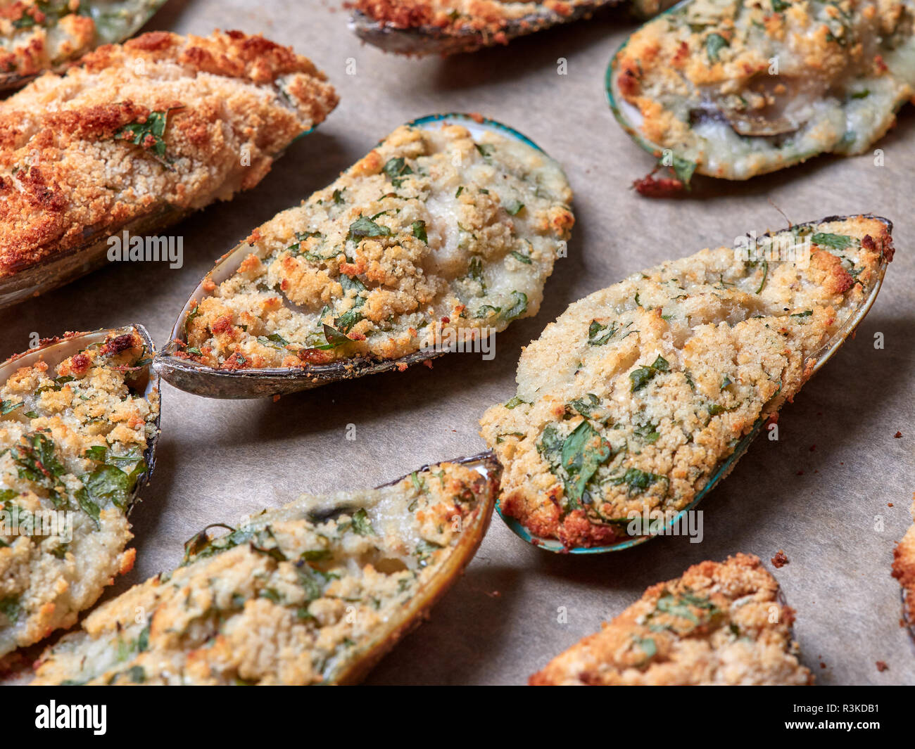 Closeup view of a tray of delicious mussels au gratin, just taken out of the oven - Stock Image