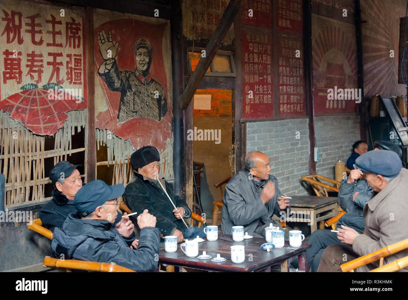 92b21ce02 Old man smoking a pipe in a teahouse decorated with Cultural Revolution-era  portrait of Chairman Mao, Pengzhen, Chengdu, Sichuan Province, China