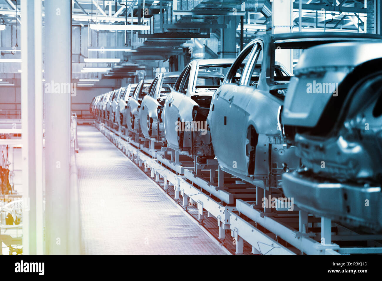 Car bodies are on Assembly line. Factory for production of cars in blue. Modern automotive industry. Blue tone - Stock Image