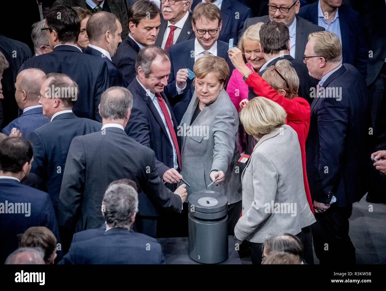 Berlin, Germany. 23rd Nov, 2018. After the 3rd reading, Chancellor Angela Merkel (CDU) interjects her voting card in the Bundestag for the adoption of the federal government's draft budget law for 2019. Credit: Michael Kappeler/dpa/Alamy Live News - Stock Image