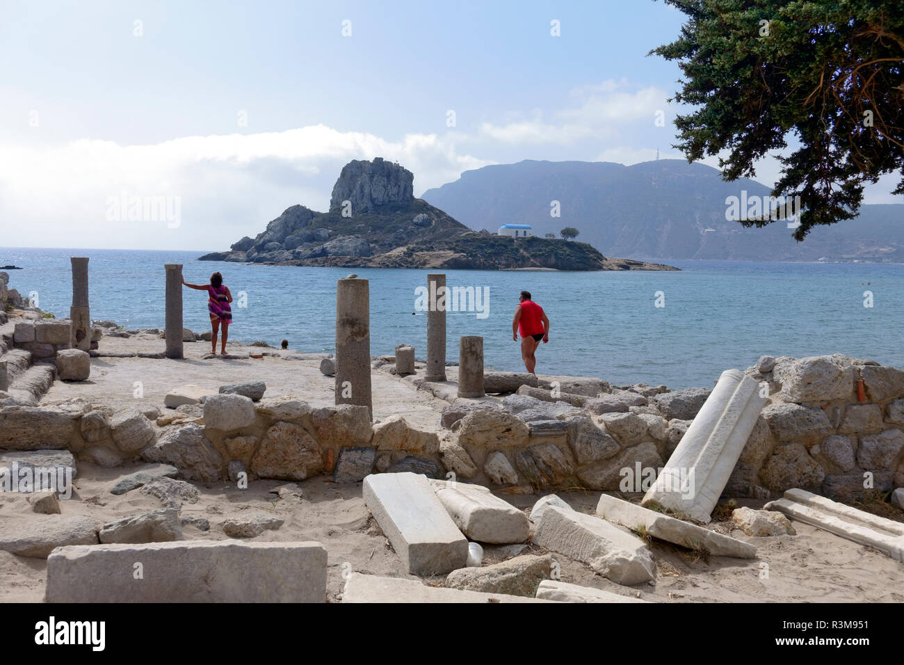 Tourists exploring the ruins of the Basilica of Ayious Stefanos at Kamari on the Greek island of Kos. The island of Kastri is also seen in the bay. - Stock Image