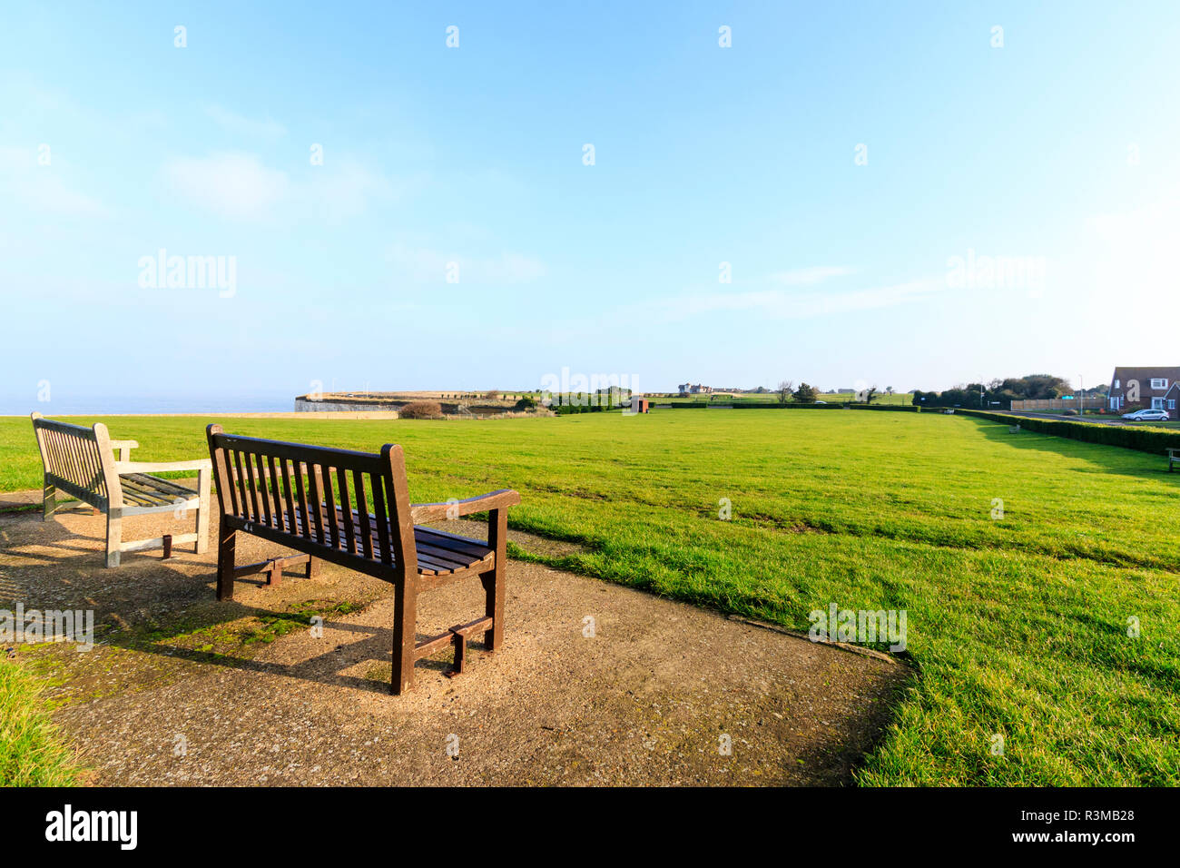 Epple Bay, Birchington, Kent. Two park benches on grass area with the coast road, bay, and golf course in the background. - Stock Image