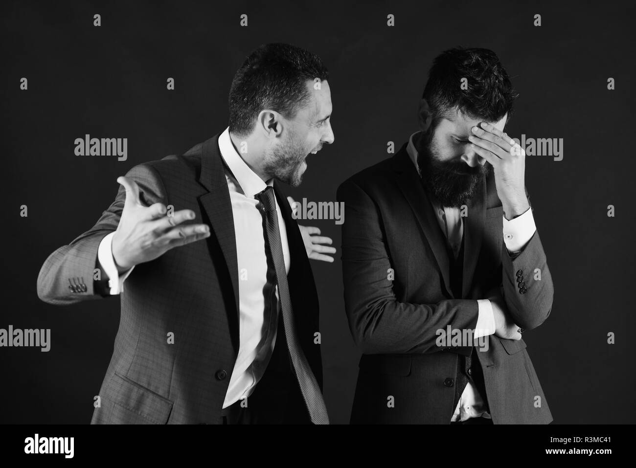 Businessmen quarreling loudly on black background. Business opposition concept - Stock Image