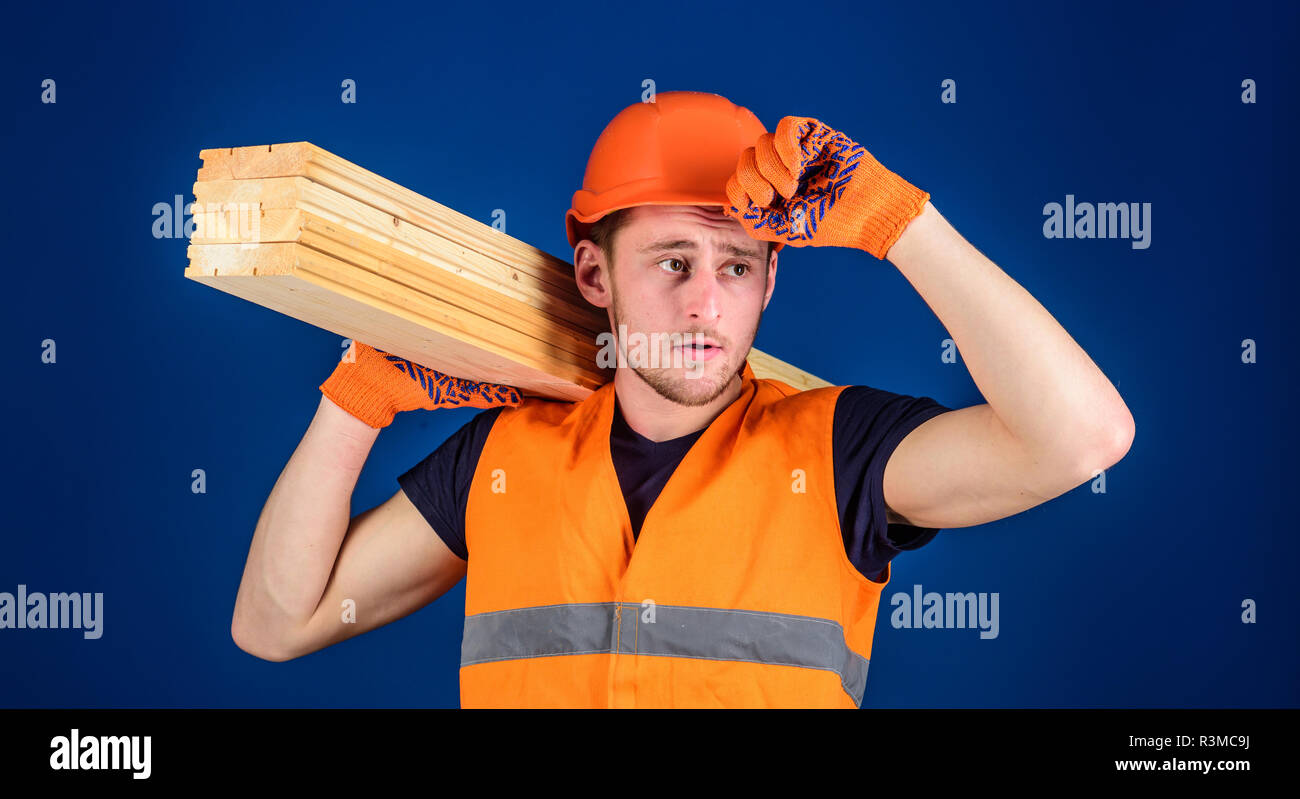 Carpenter, woodworker, labourer, builder carries wooden beam on shoulder. Protective equipment concept. Man in protective gloves holds visor of helmet Stock Photo