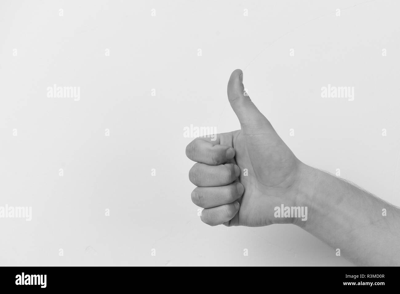 Male hand shows thumbs up sign. Gesture expresses approval. Hand isolated on light grey background. Body language concept. - Stock Image