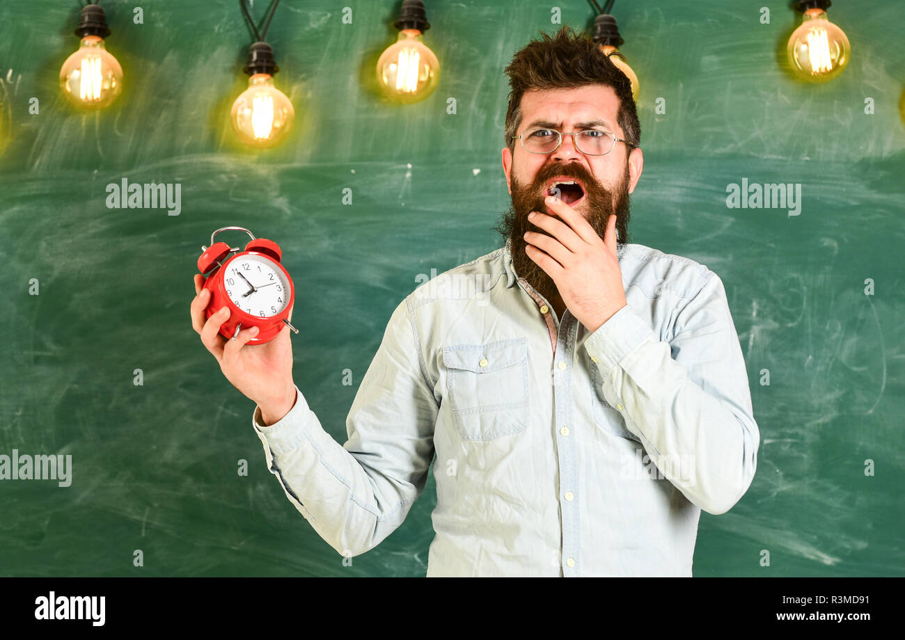 Forgot about time concept. Bearded hipster holds clock, chalkboard on background, copy space. Teacher in eyeglasses holds alarm clock. Man with beard  - Stock Image