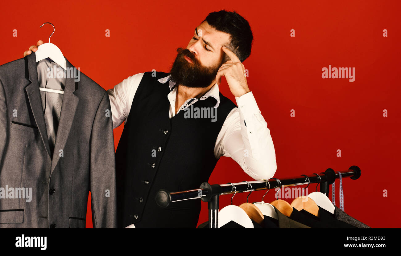 Man with beard in vest by clothes rack. Designer looks at his work near clothes hangers. Tailor with thoughtful face holds grey suit near custom jacke - Stock Image