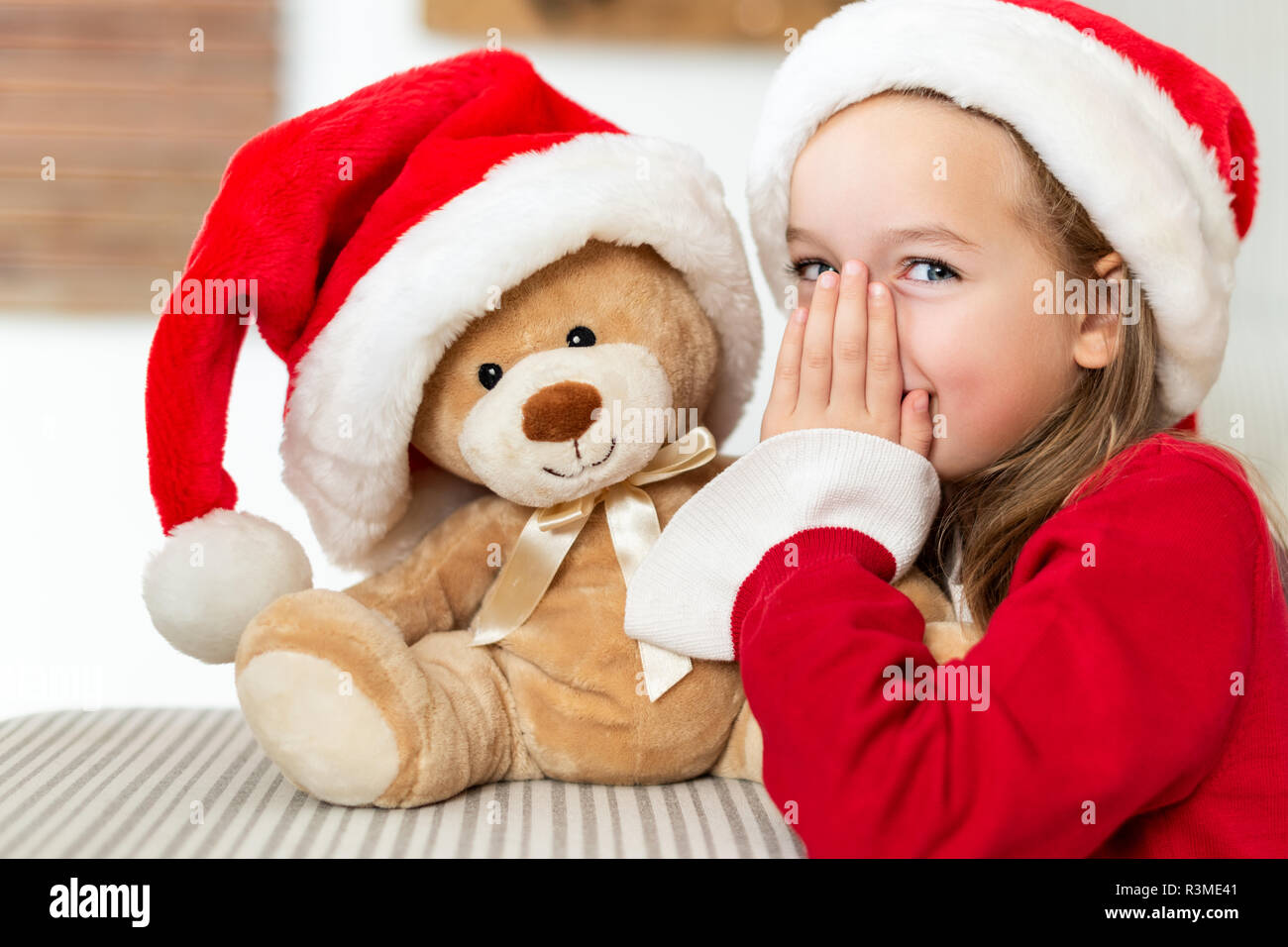 da3cc2fd0507a Cute young girl wearing santa hat whispering a secret to her teddy bear  christmas present toy