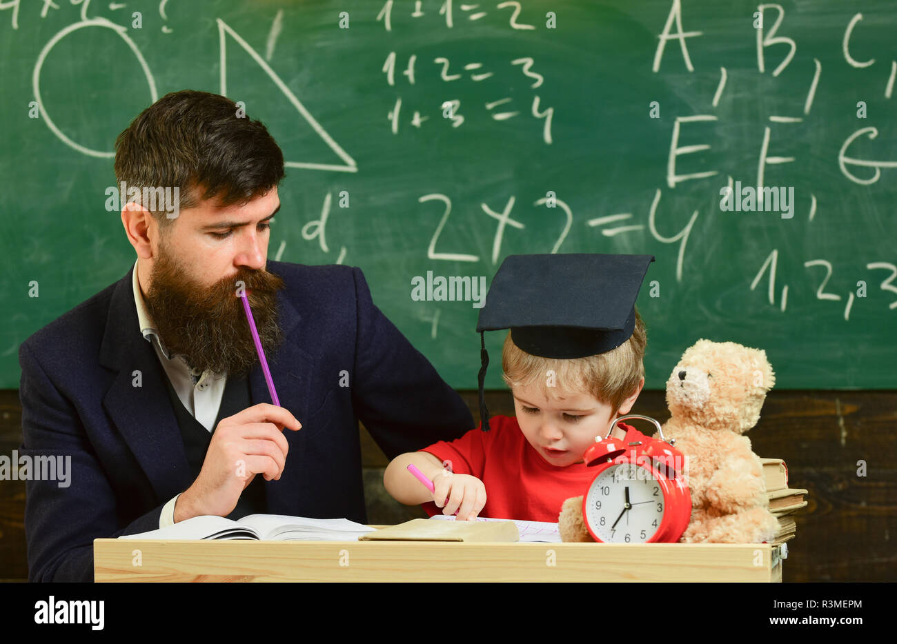 Father checking hometask, helps to boy, son. Teacher in formal wear and pupil in mortarboard in classroom, chalkboard on background. Hometask concept. - Stock Image