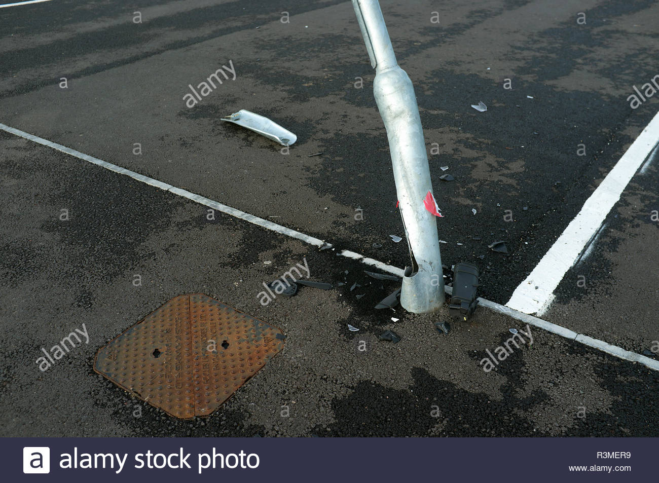 Car park damage - a bent lamp post with vehicle debris at base. UK. Stock Photo