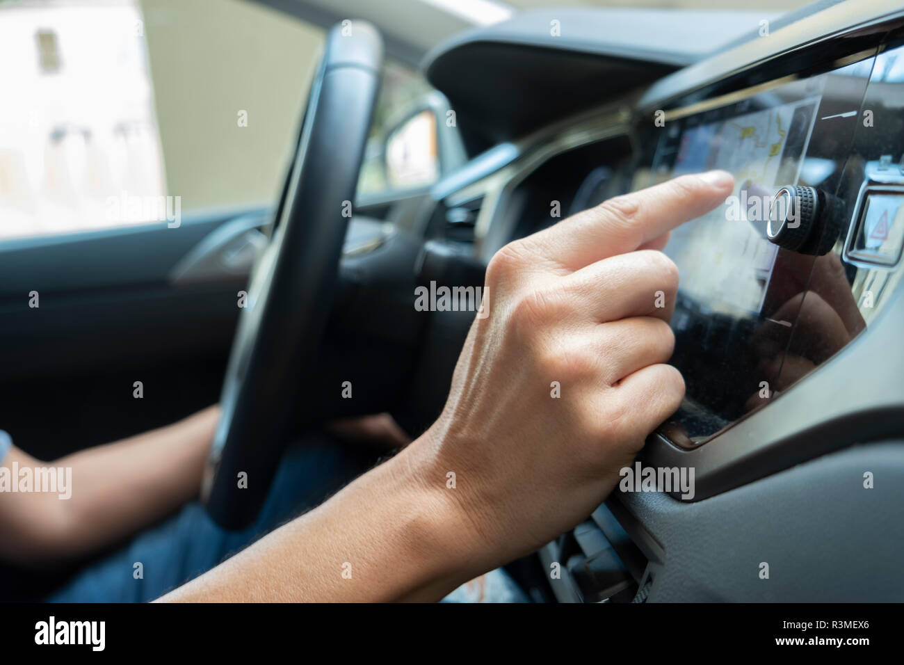 closeup of a young caucasian man using the automotive navigation system of a car - Stock Image