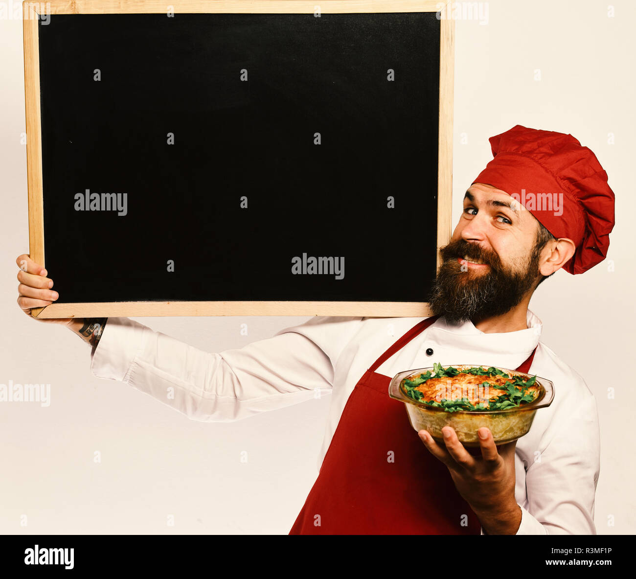 Catering and open day concept. Cook with tricky smile in burgundy uniform holds baked dish and blackboard. Chef holds bowl with potato casserole and b - Stock Image