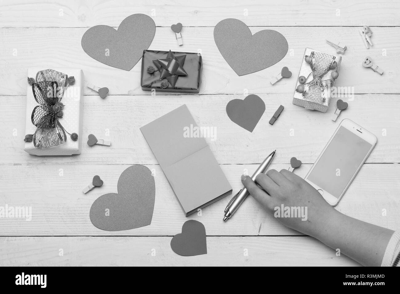 Valentines day cards, decorations and presents, top view. Love and holiday concept. Female hand holding pen. Paper hearts, notes, mobile phone and peg - Stock Image