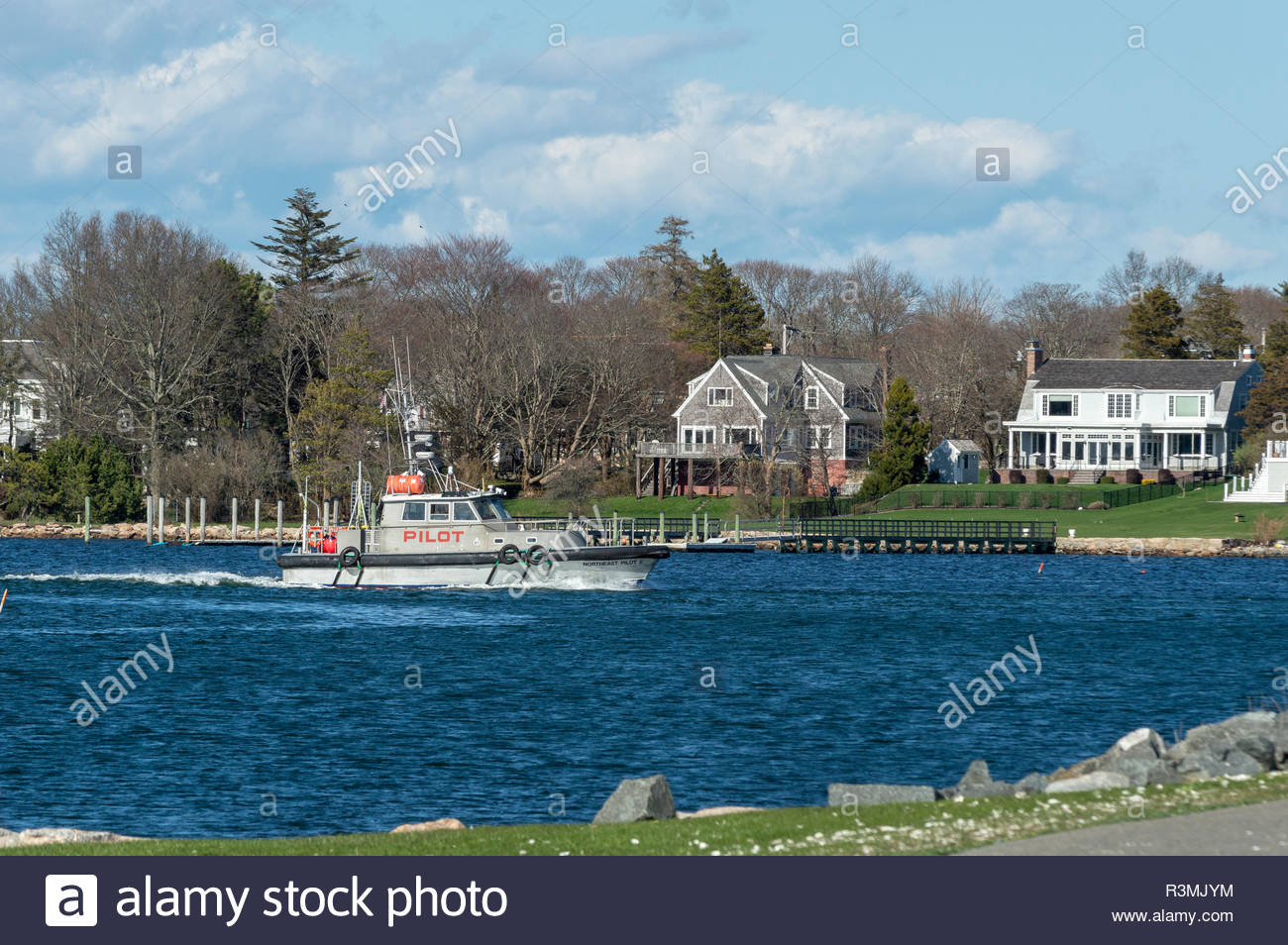 New Bedford, Massachusetts, USA - April 26, 2018: Pilot boat Northeast Pilot II approaching hurricane barrier with Fairhaven residences in background - Stock Image