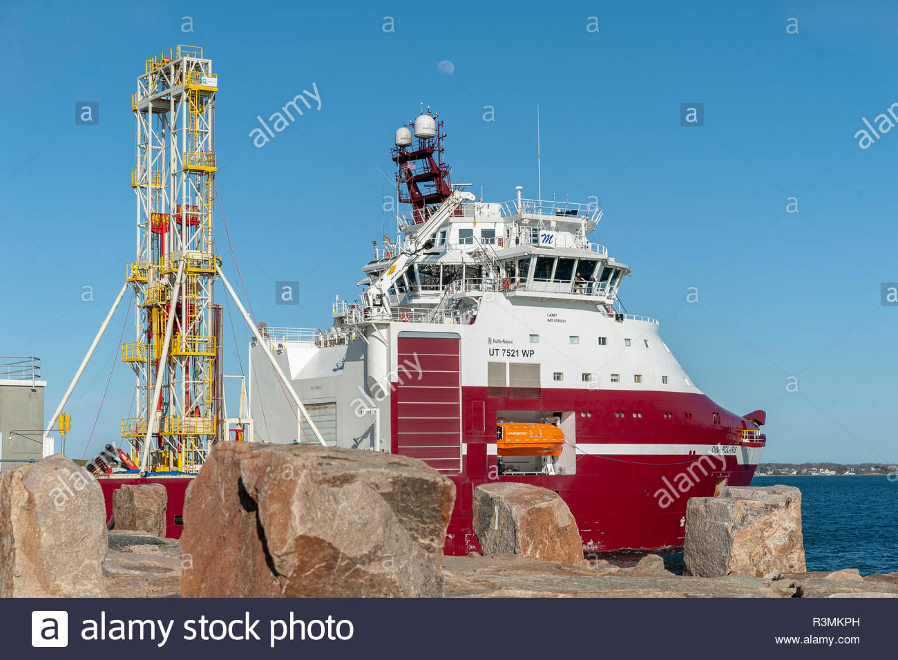 New Bedford, Massachusetts, USA - April 26, 2018: Moon over geotechnical drilling vessel Dina Polaris as it passes through hurricane barrier - Stock Image