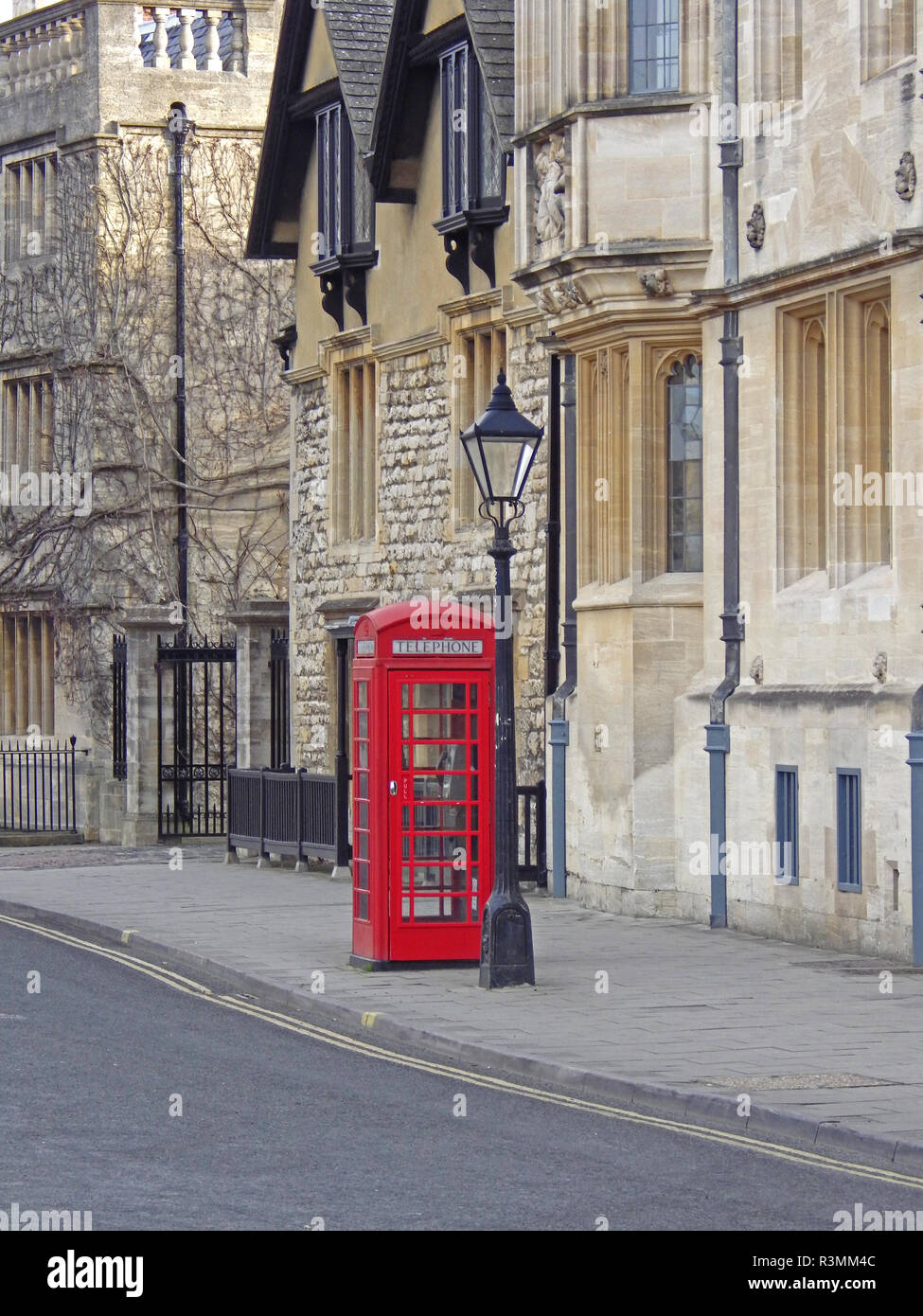 typical English red phone box or booth in Oxford city centre in St Giles' outside the Lamb and Flag pub - Stock Image