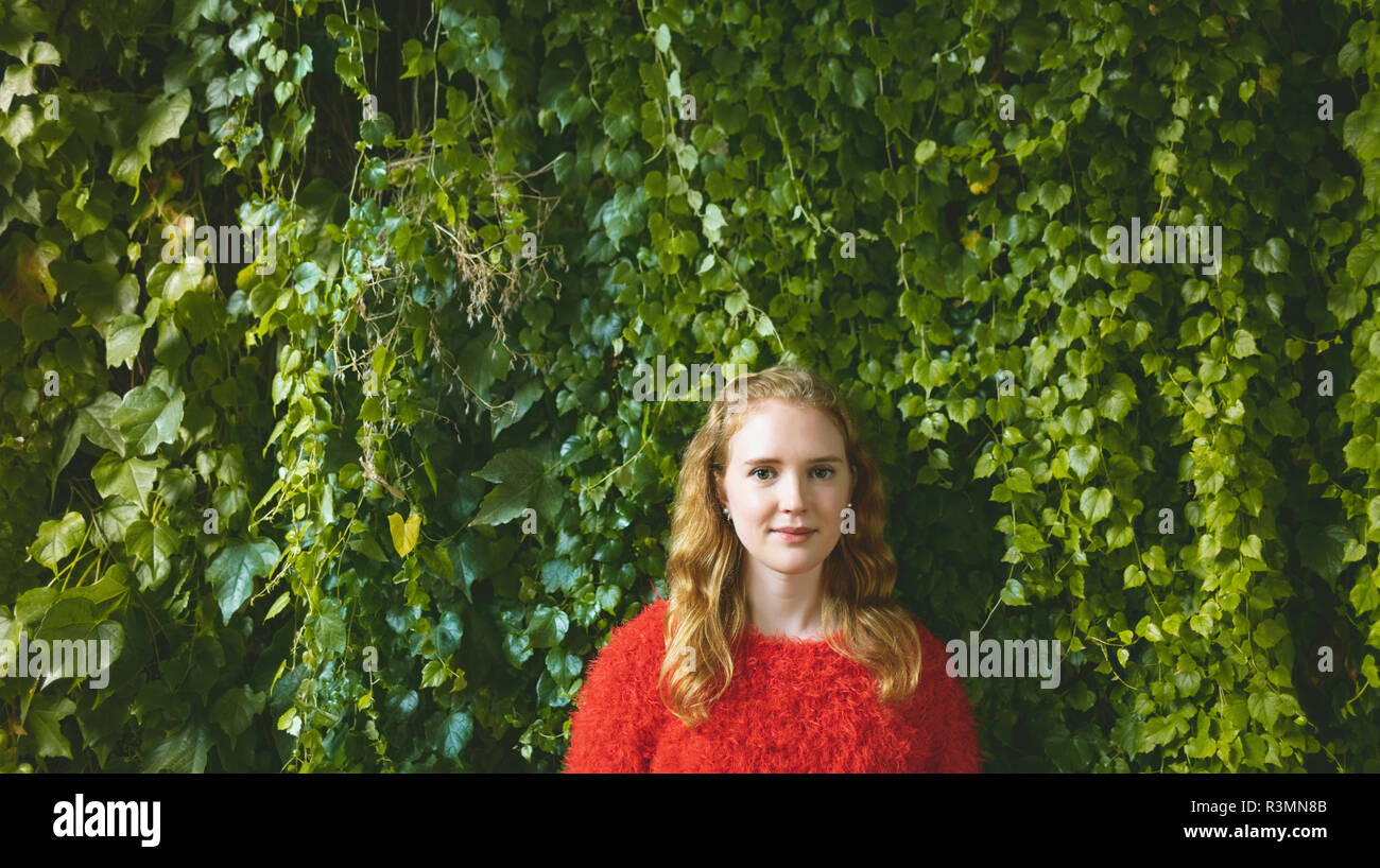 Woman standing against plant creeper in outdoor cafe - Stock Image