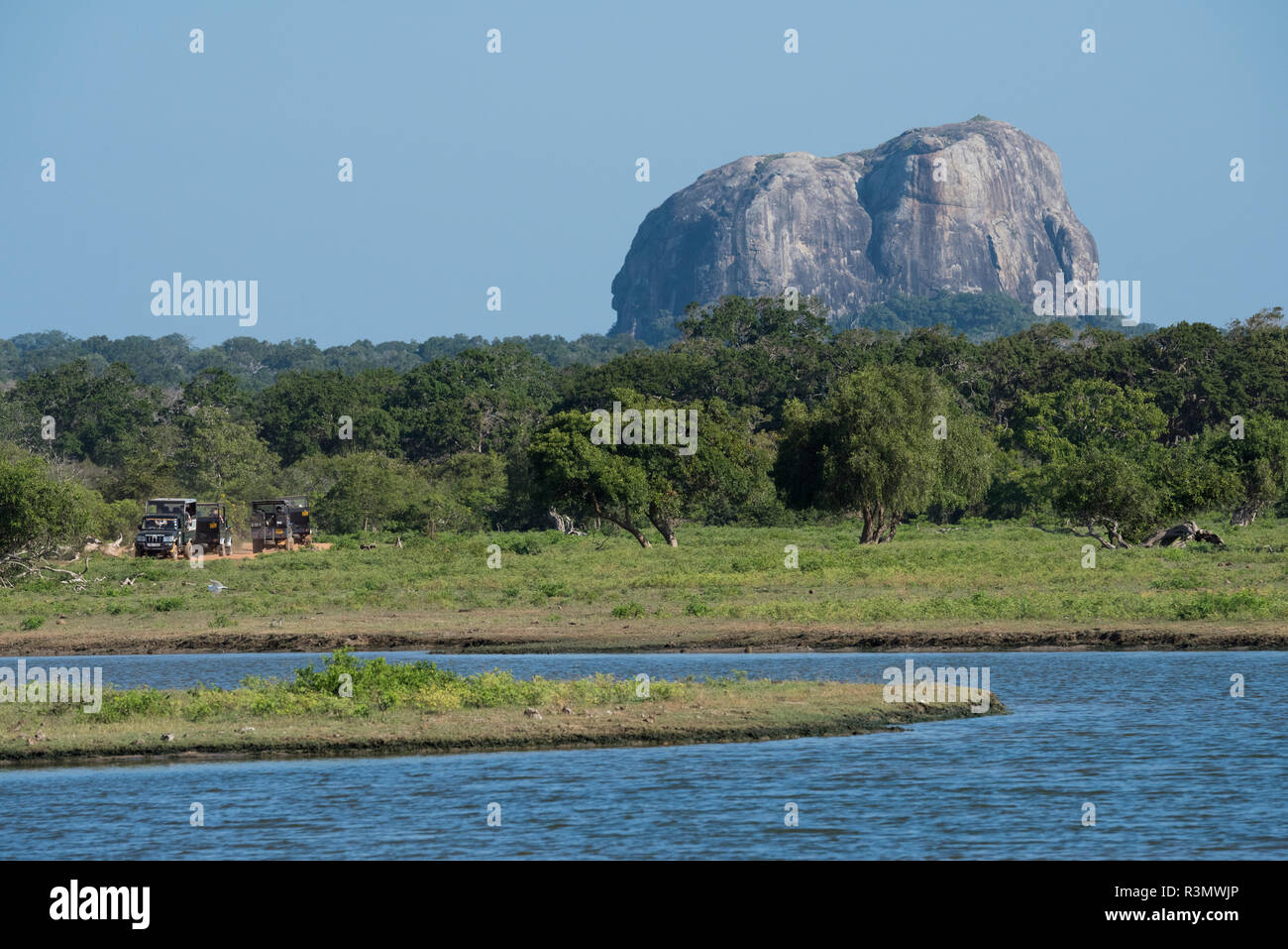 Sri Lanka, Yala National Park, aka Ruhuna National Park (block 1) est. in 1900. Scenic view of landmark Elephant Rock, game drive jeeps on road. - Stock Image