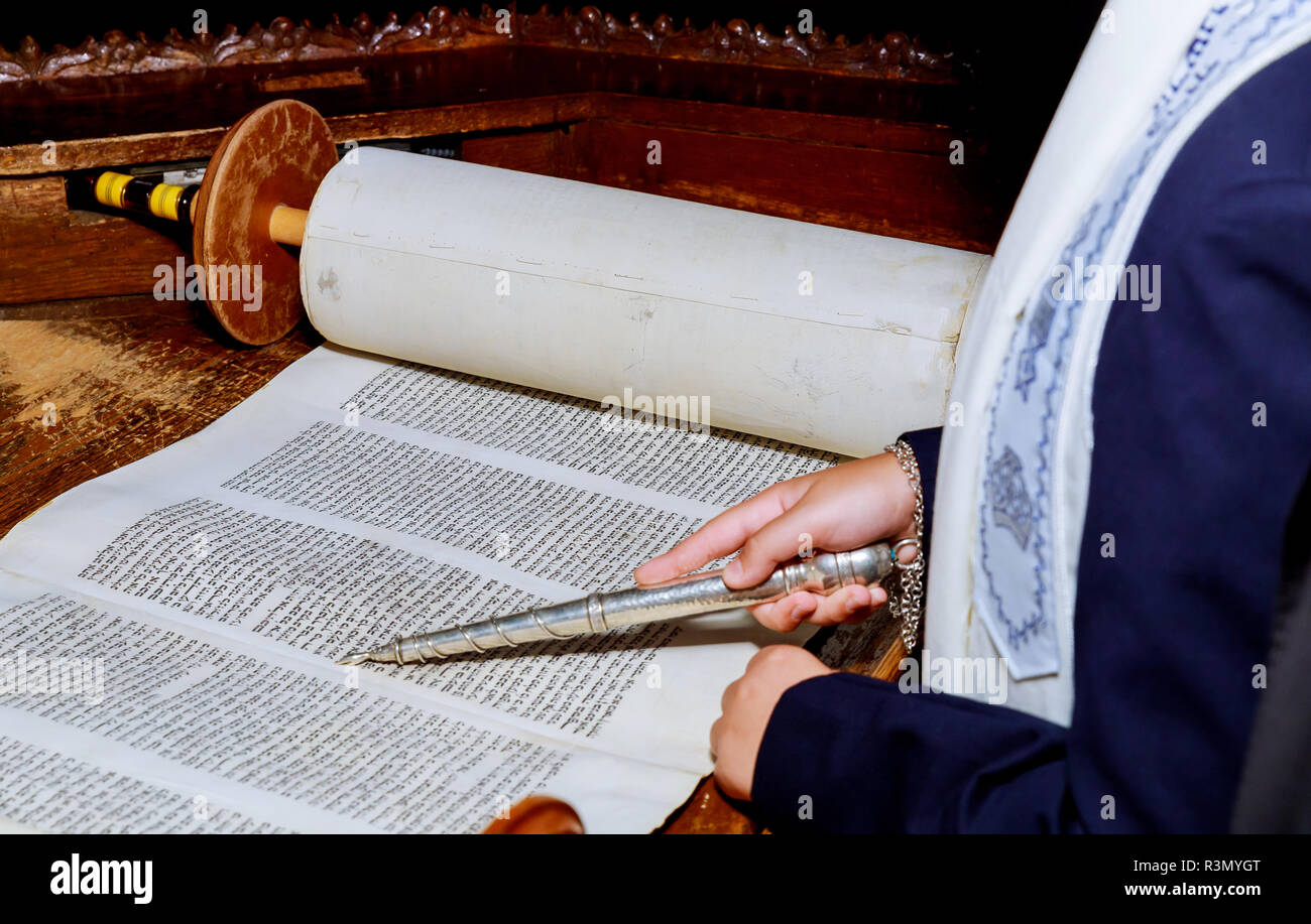 Hand of boy reading the Jewish Torah at Bar Mitzvah Bar Mitzvah Torah reading - Stock Image