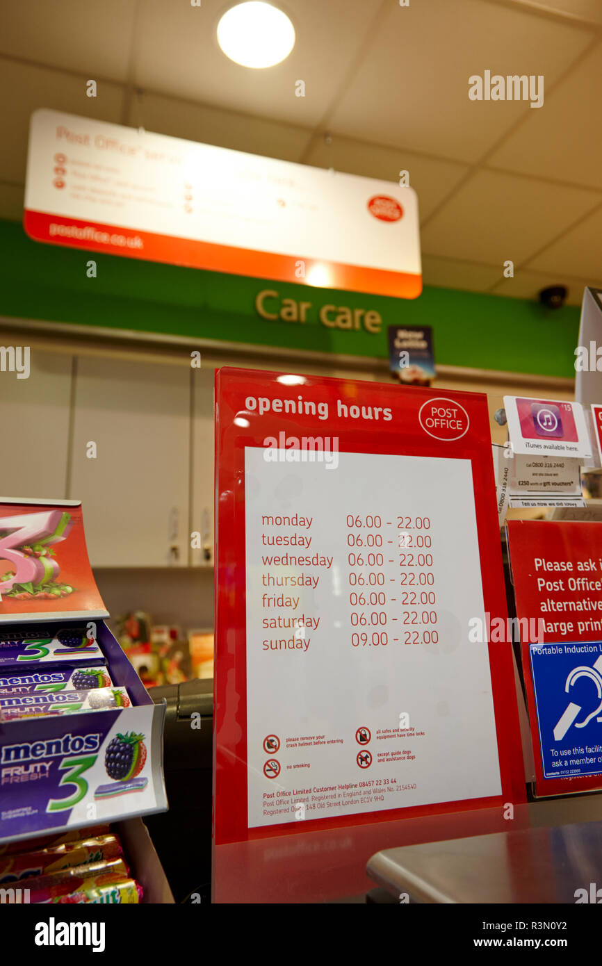 Post Office counter in a local service station supermarket showing early to late opening hours - Stock Image
