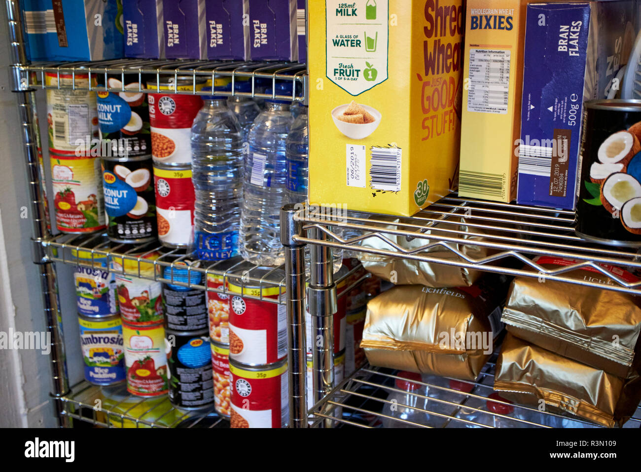 canned goods powdered milk cereals and bottled water stored in case of emergency - Stock Image