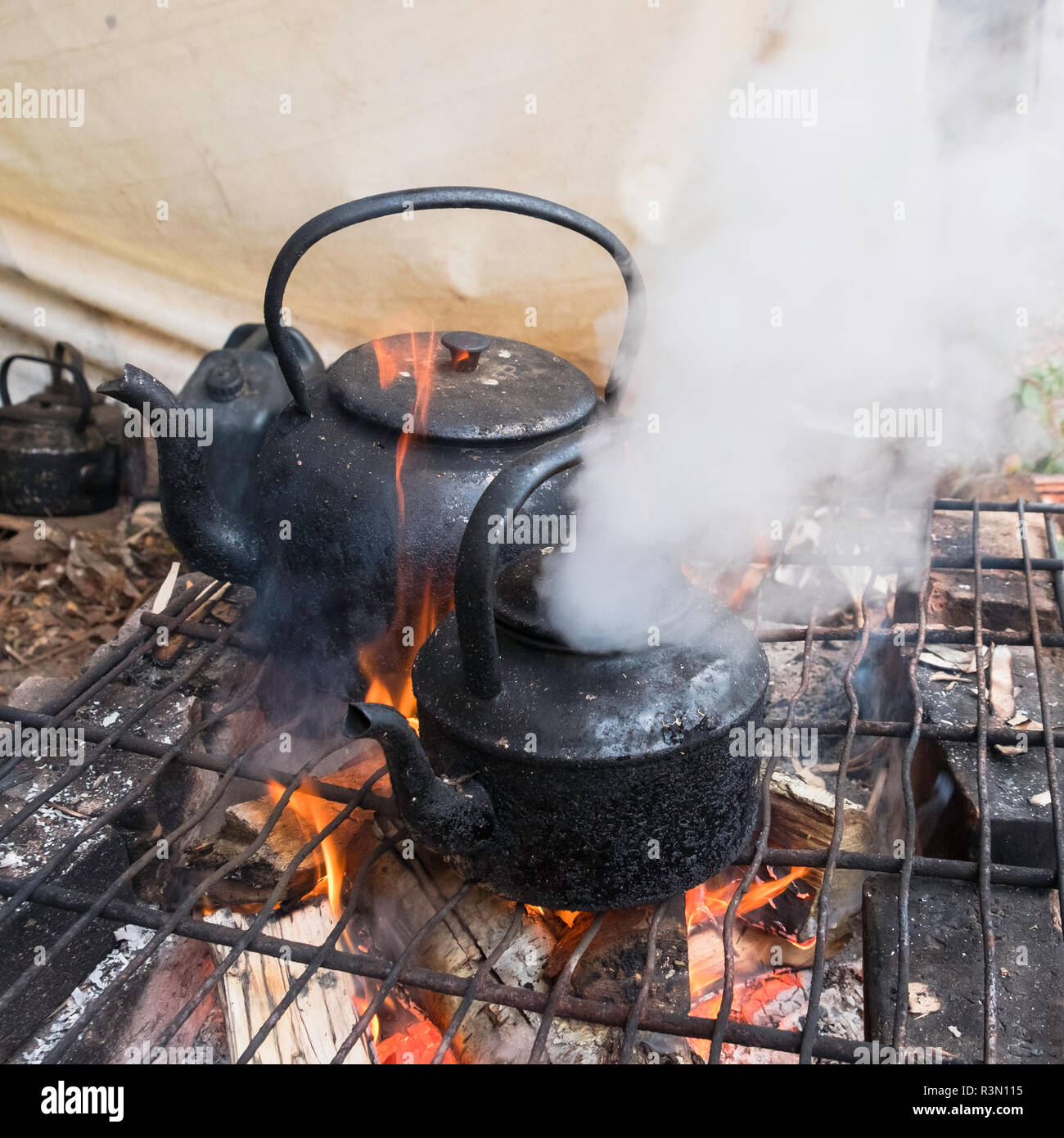 Kettle boiling over an open fire. - Stock Image