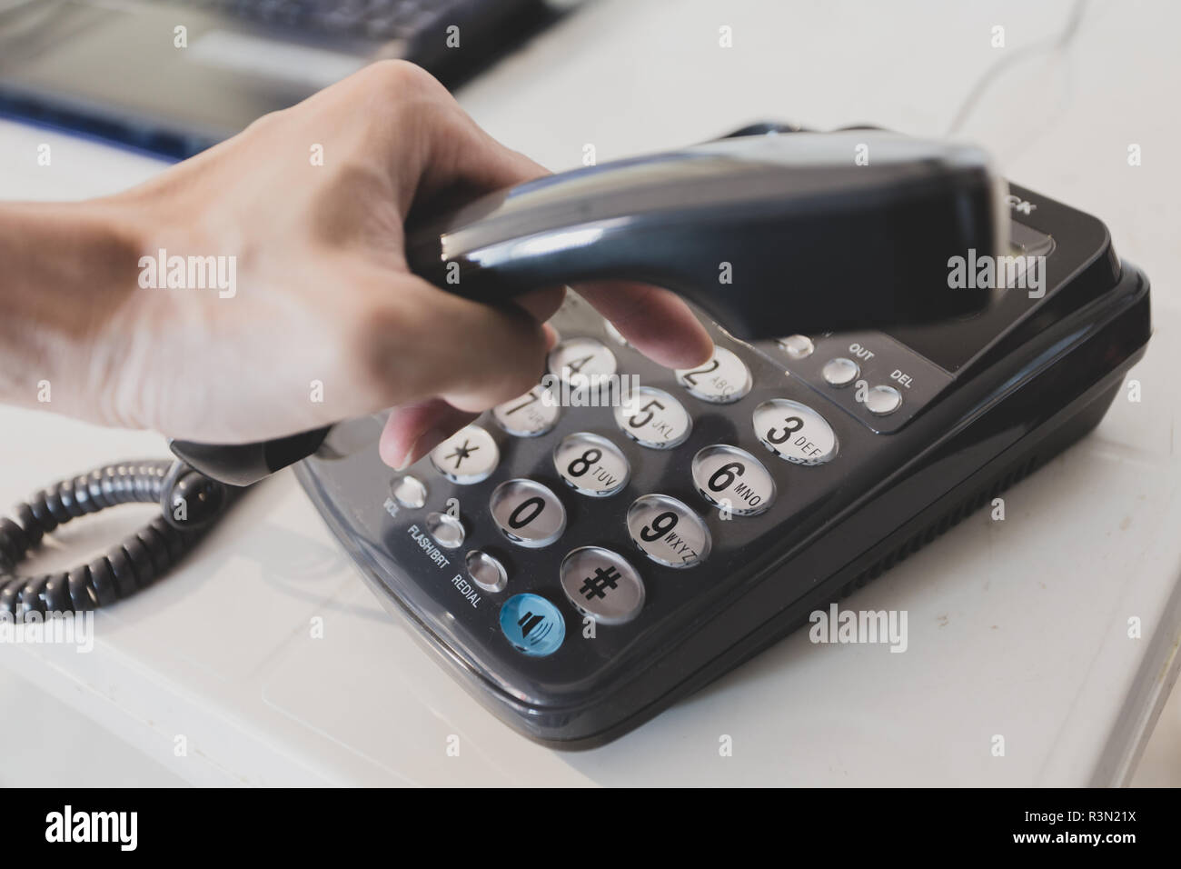 Closeup of male hand holding telephone receiver while dialing a phone number to make a call - Stock Image