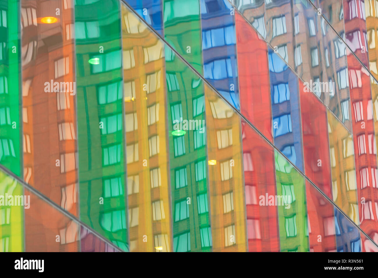 Building reflecting in colorful windows of Montreal Convention Center, International Quarter, Montreal, Quebec, Canada - Stock Image