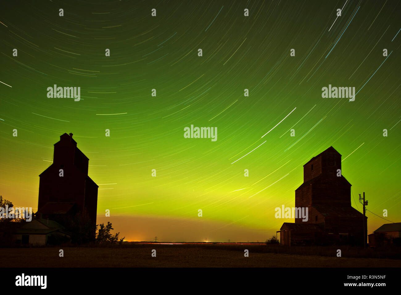Canada, Saskatchewan, Lepine. Aurora borealis and star trails silhouette grain elevator. - Stock Image