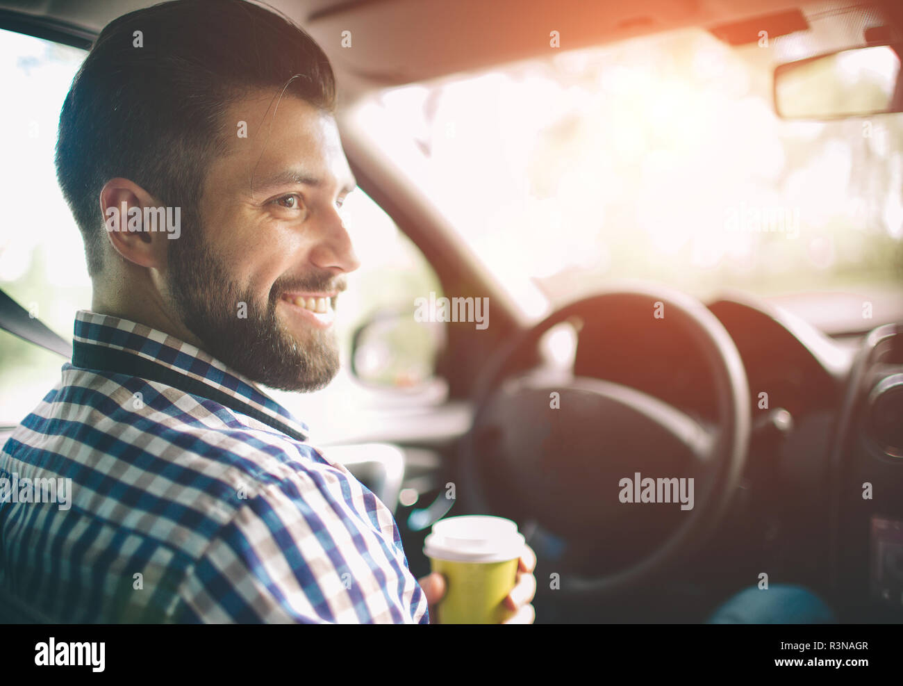 Beautiful woman smiling while sitting on the front passenger seats in the car - Stock Image