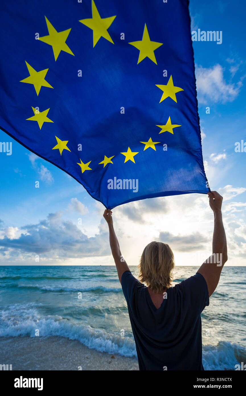 European Union flag flying in bright morning sunlight held up by man with blond hair standing on empty Mediterranean beach - Stock Image