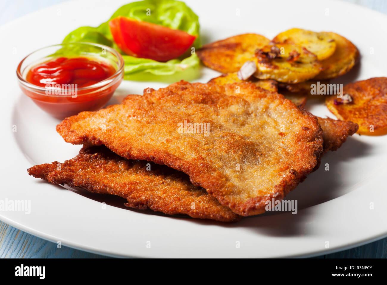 wiener schnitzel with fried potatoes Stock Photo