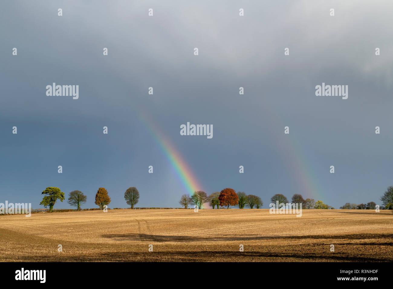 Autumn rainbow and dark skies over Northamptonshire countryside. UK - Stock Image