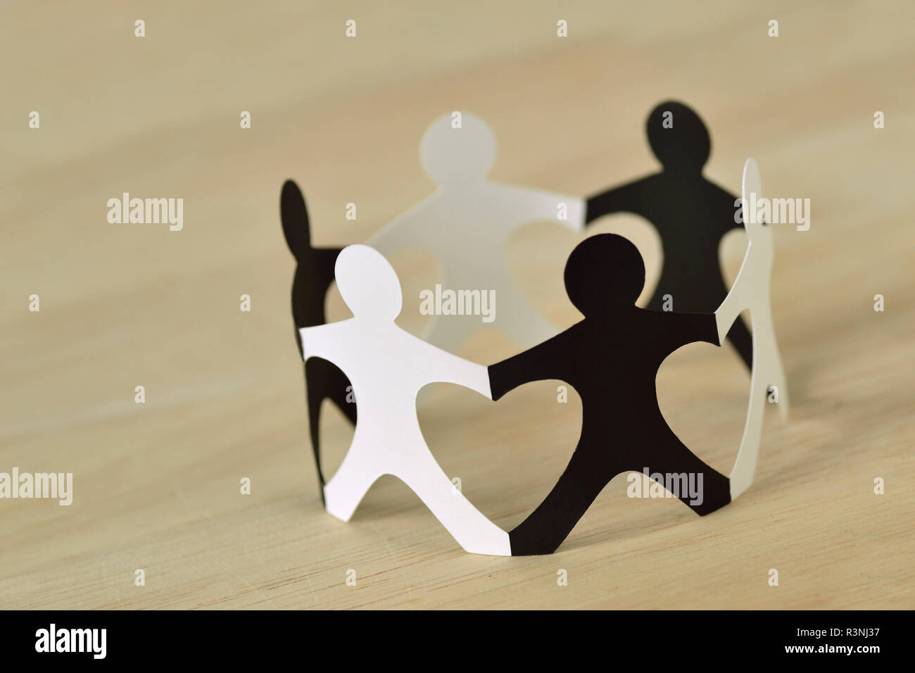 Black and white paper people in a circle holding hands - Anti-racism concept - Stock Image