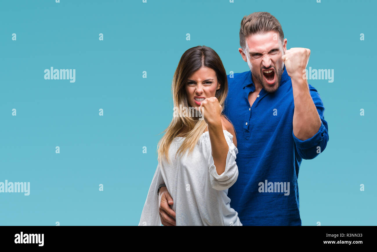 Young couple in love over isolated background angry and mad raising fist frustrated and furious while shouting with anger. Rage and aggressive concept - Stock Image