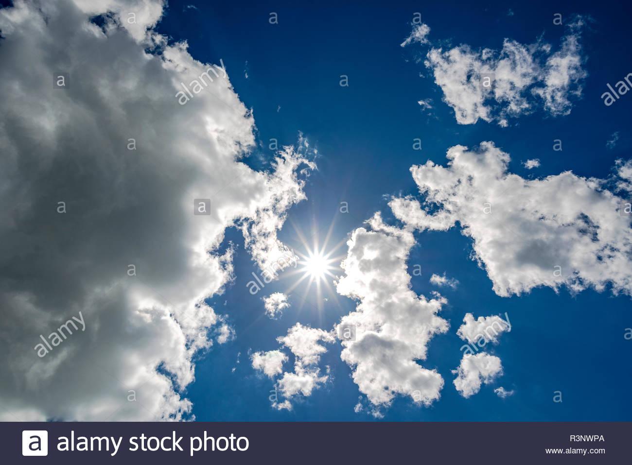 Strahlende Sonne im zwischen Wolken am dunkelblauen Himmel - Stock Image