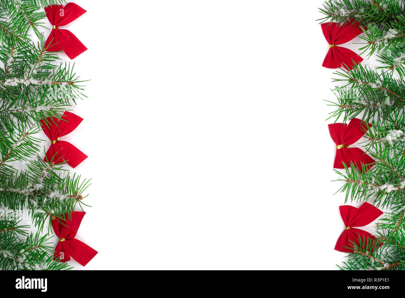 Christmas Frame of Fir tree branch with snow and red bows isolated on white background with copy space for your text - Stock Image