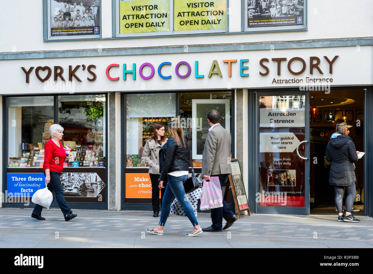 People walking past York's Chocolate Story (interactive museum attraction) as visitors go through the entrance - York, North Yorkshire, England, UK. Stock Photo