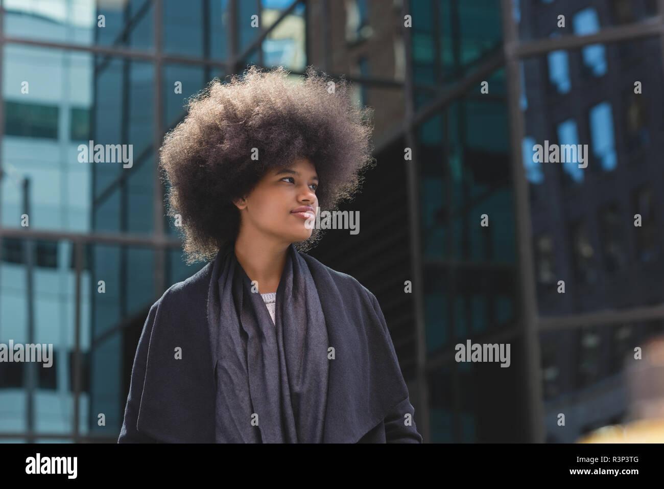 Afro woman walking on street - Stock Image