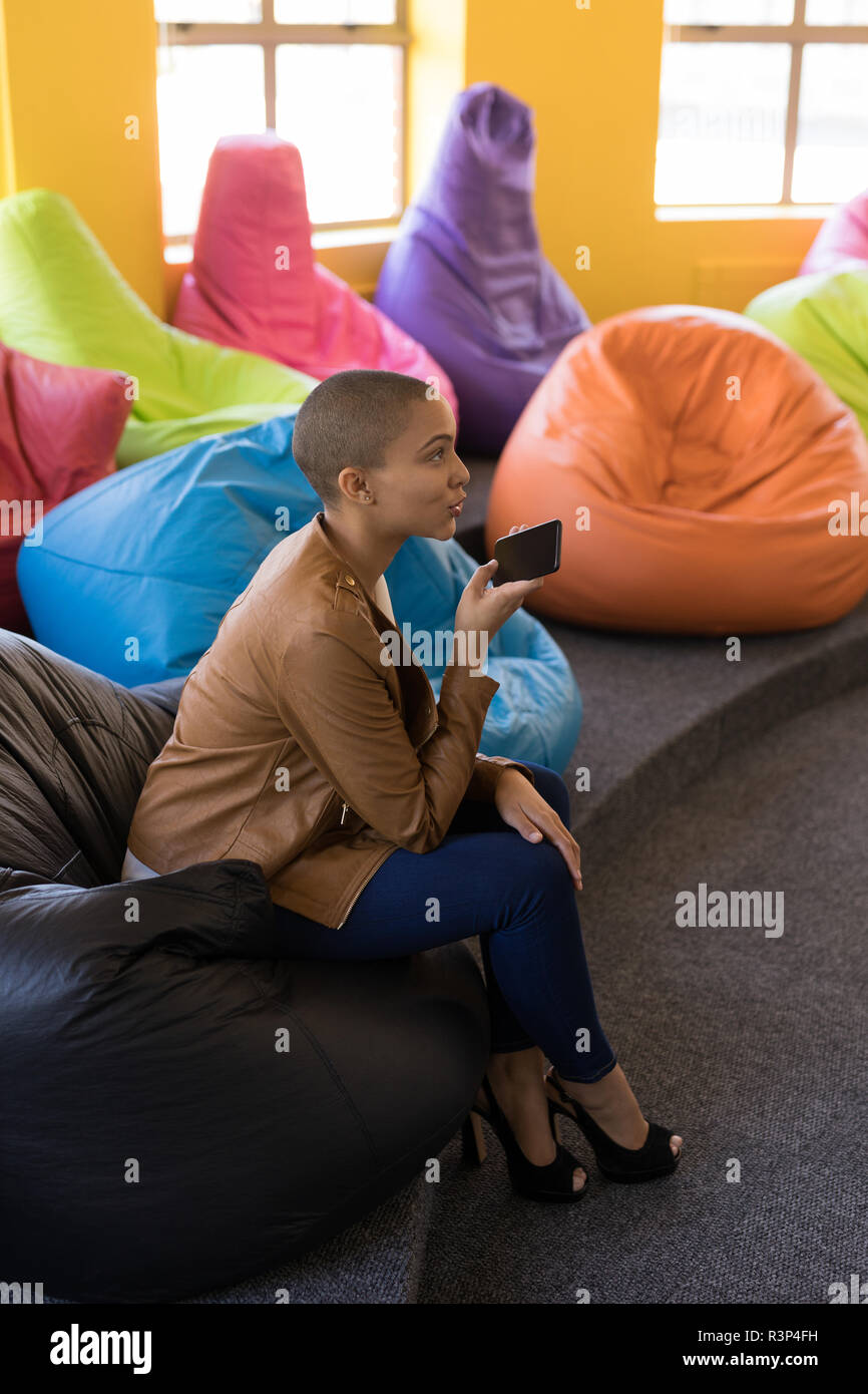 Business executive talking on mobile phone while sitting on bean bag - Stock Image