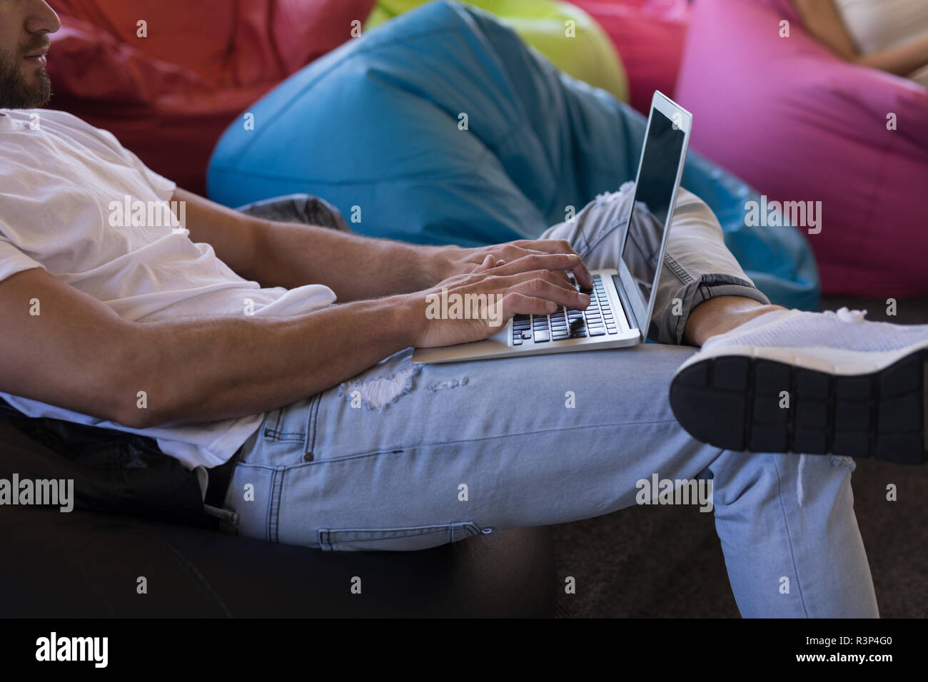 Business executive using laptop while sitting on bean bag - Stock Image