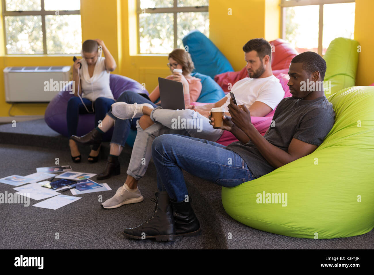Business executives working while sitting on beanbag - Stock Image
