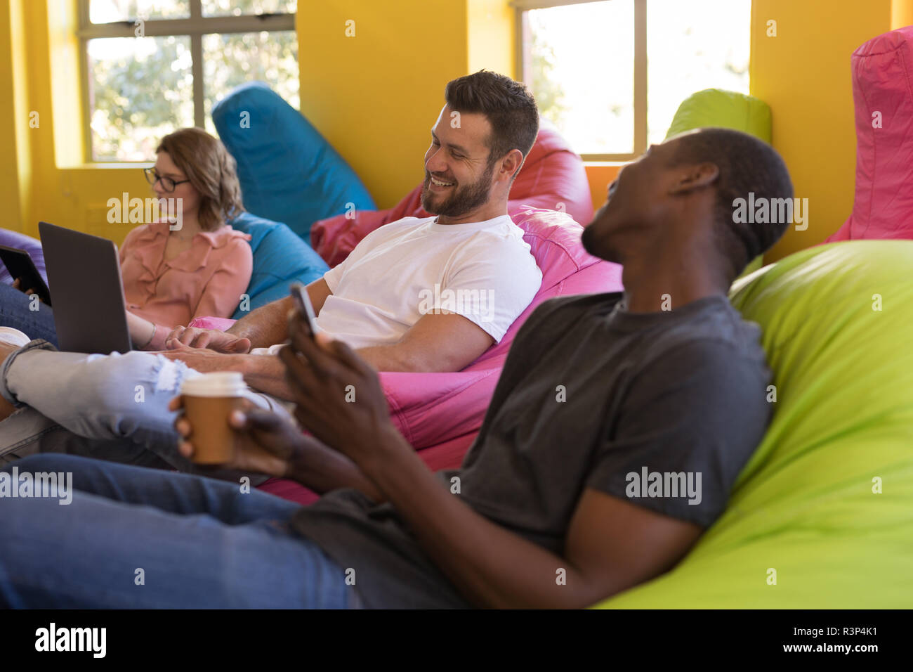 Business executives talking with each other while sitting on bean bag Stock Photo