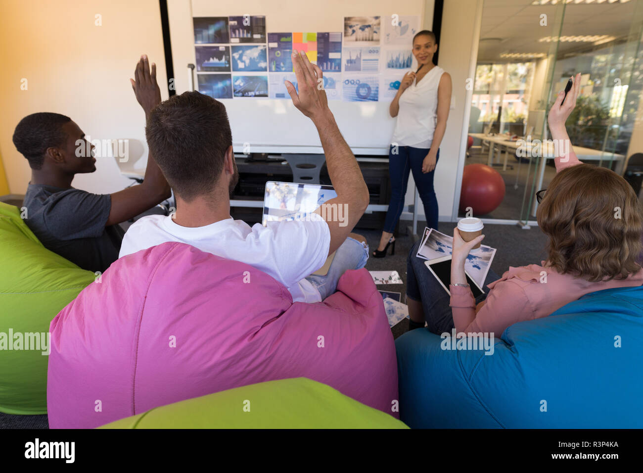 Business executives hand raised while sitting on bean bag during meeting - Stock Image